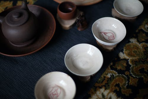 From above set of oriental tea cups placed on rug with teapot during traditional ceremony