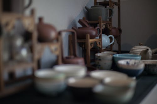 Various ceramic teapots in different shapes and traditional Asian cups placed on table in kitchen