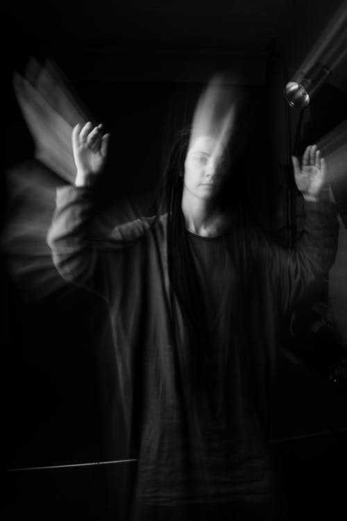 Woman in cassock with raised arms in dark room