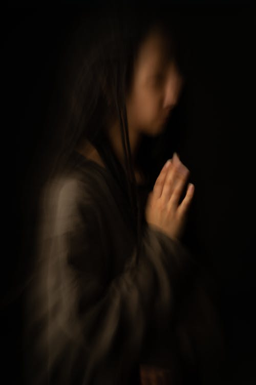 Side view of melancholic blurred female passing away in obscurity against black background