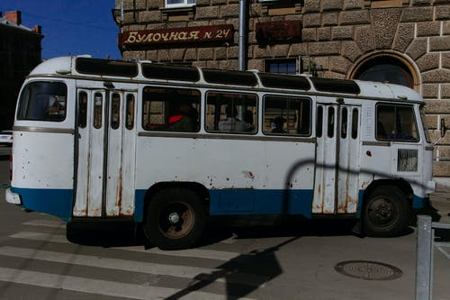 Old fashioned rusty bus with people driving on intersection at corner of city street