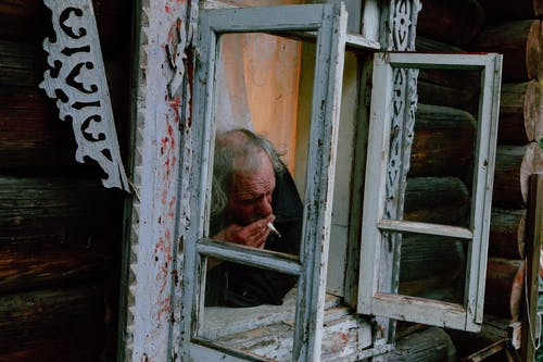 Senior male with gray hair smoking cigarette through opened window of shabby rural  house