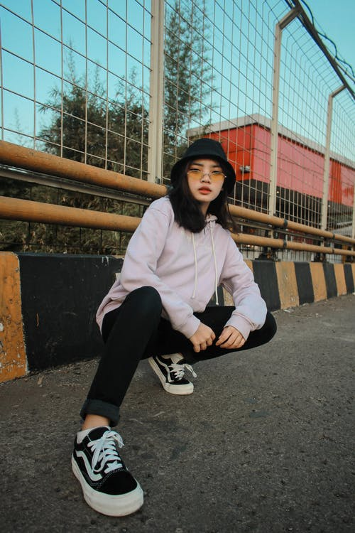 Woman in White Long Sleeve Shirt and Black Pants Sitting on Concrete Stairs