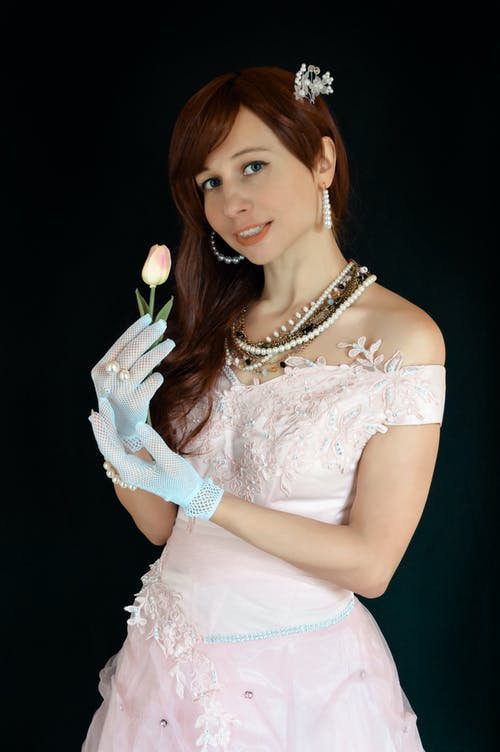 Positive young female with toothy smile wearing elegant dress and gloves with beads standing against black background and looking at camera