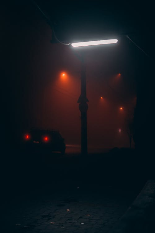 Silhouette of taillights of car and flashlights of city in haze at night