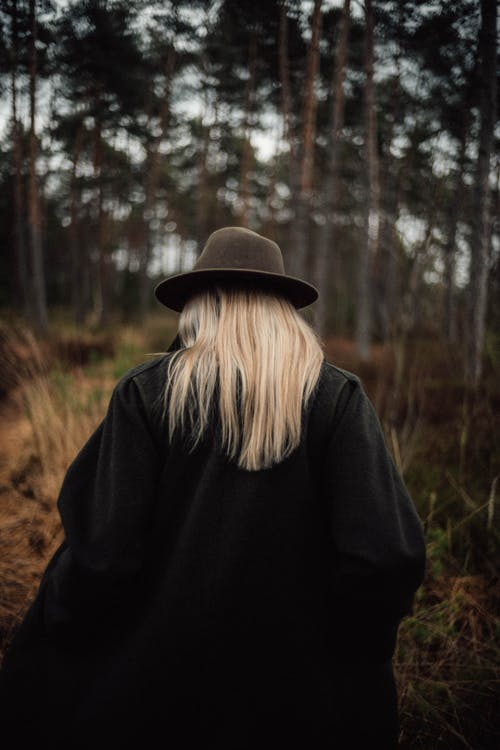 Woman in Black Jacket Wearing Brown Hat Standing in Forest
