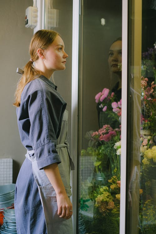 Woman in Blue Long Sleeve Dress Standing Beside the Flowers