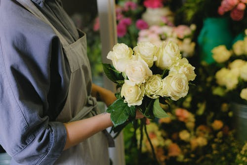 Person Holding White Roses Bouquet