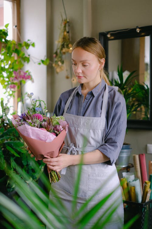 Woman in Blue Long Sleeve Shirt Holding a Bouquet of Flowers