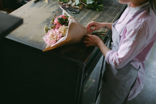 Person in Pink Long Sleeve Shirt  Arranging Flowers