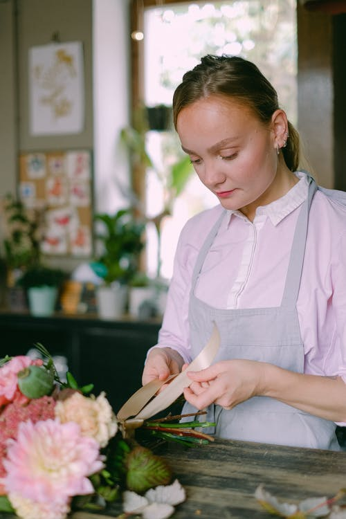 Woman in Pink Long Sleeve Shirt Arranging Flowers
