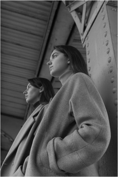 Low angle of confident female models in stylish clothes standing on railway station and looking away