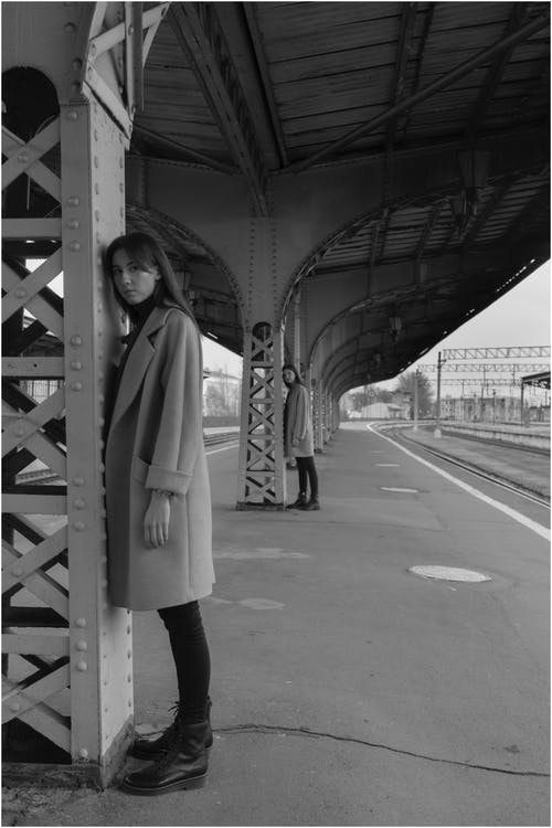 Full body of female models in trendy clothes standing near iron pillars on railway platform and looking at camera