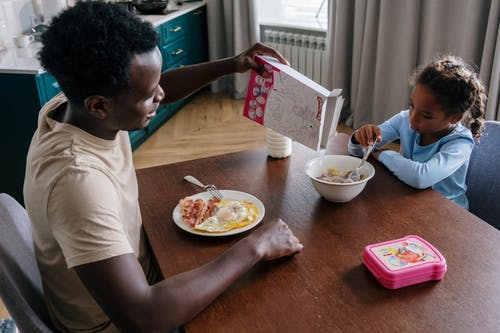 Father and Daughter Eating Breakfast on the Table
