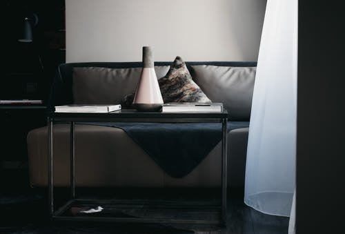 Stylish vase and books arranged on table placed near comfortable leather couch in modern apartment