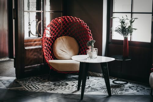 Trendy chair and table decorated with green plants in modern cafe