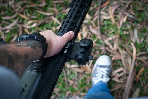 Person Holding Black Rifle Gun with Scope