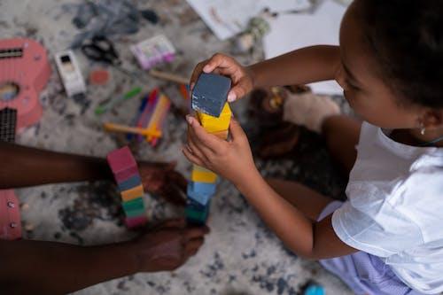 Kind Im Weißen Trägershirt, Das Gelbes Und Blaues Plastikspielzeug Hält