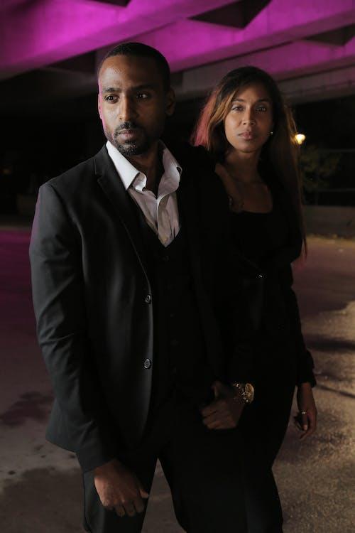 Man in Black Suit Jacket Beside Woman in Black Dress