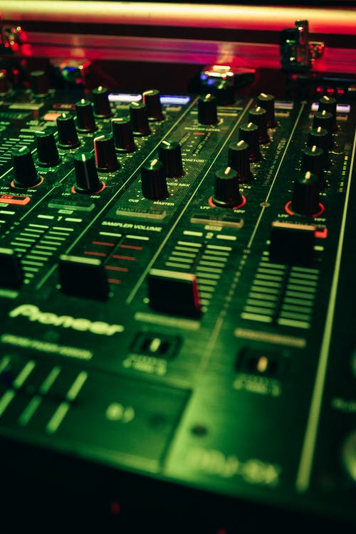 Modern mixing console with rows of knobs and faders with scales on plastic panel in green light