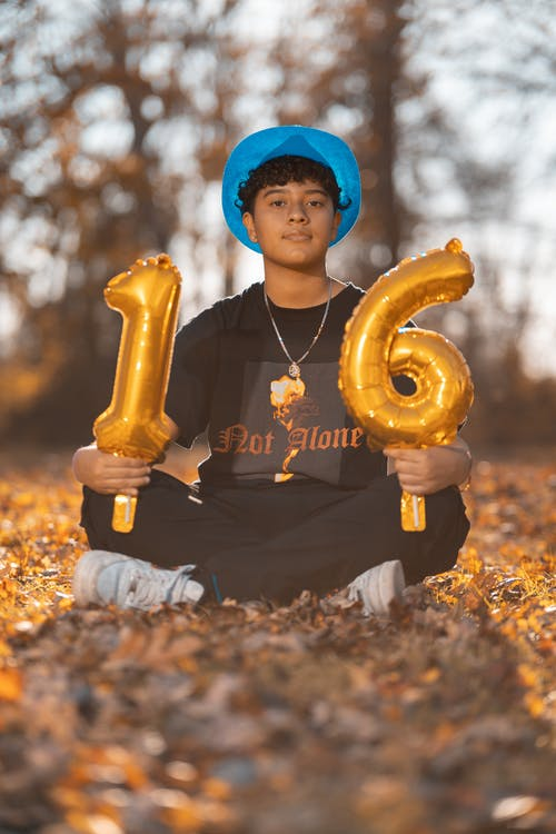 Boy in Black Crew Neck Shirt Holding Yellow Balloon