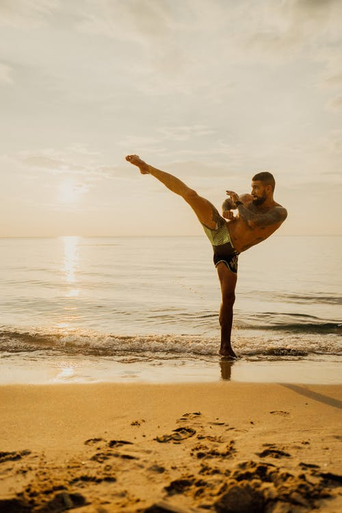 A Man Practicing Kick Boxing while on the Seashore