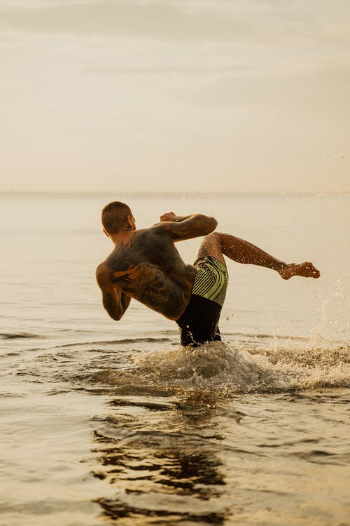 A Man Practicing Kick Boxing while on the Beach
