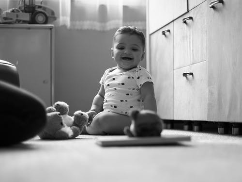 Grayscale Photo of Baby Smiling while Sitting on the Floor