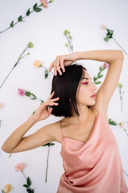 핑크 꽃을 들고 핑크 민소매 드레스 여자