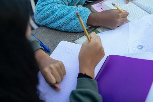 Crop faceless ethnic children sitting at table with pencils and doing homework together