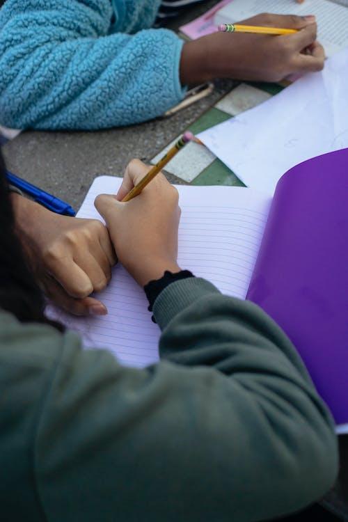 Crop ethnic children doing homework in classroom