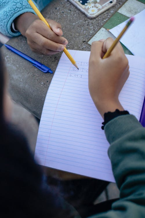 High angle of crop unrecognizable children with pencils and notebooks doing homework while sitting at table