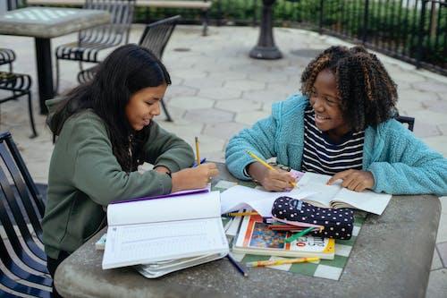 Cheerful multiethnic little girls doing homework together