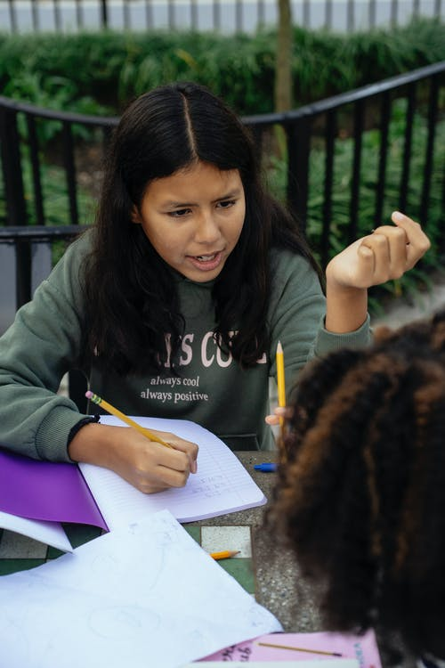 Focused Latin American kid in casual clothes sitting at table with notebook and pencil and discussing homework with friend