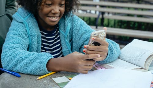Crop African American child smiling and browsing mobile phone while having break from homework