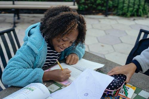 Little schoolgirl doing homework with friend