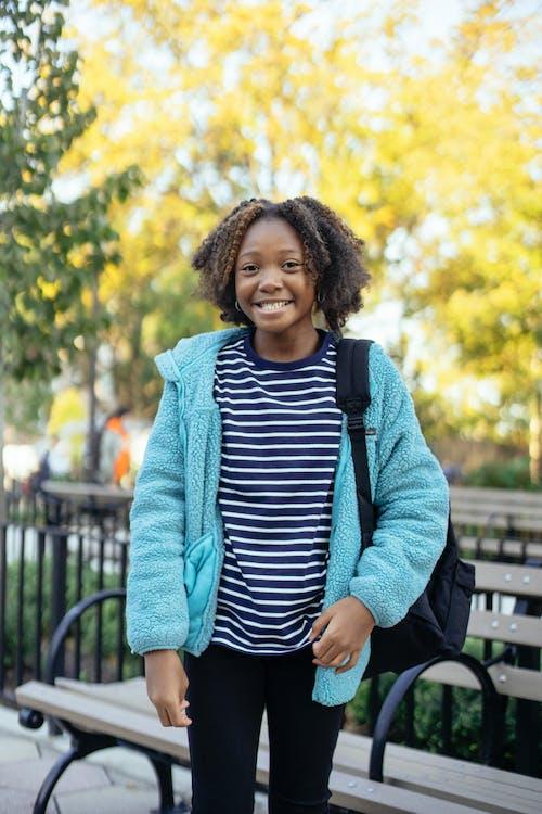 Happy black schoolgirl standing in park