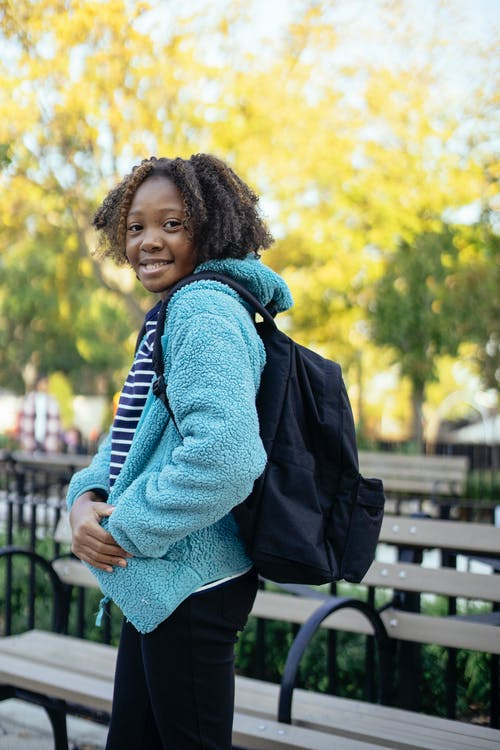 Side view of cheerful black little girl with backpack standing in park near wooden bench and looking over shoulder