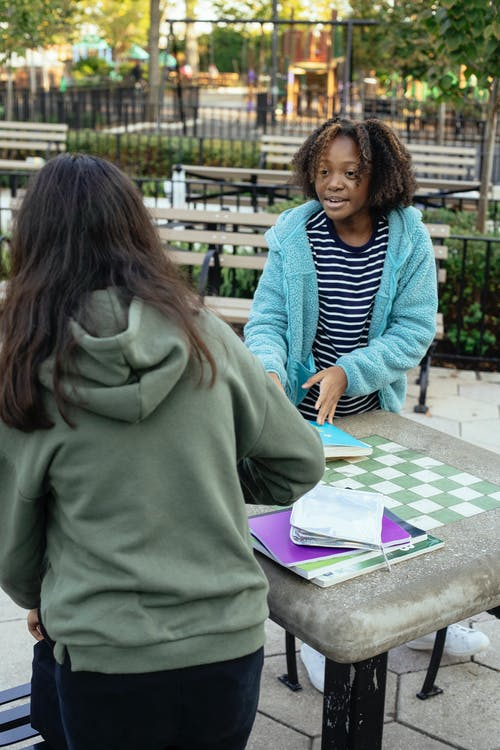 Cheerful African American little girl in casual clothes standing near table with friend and doing homework