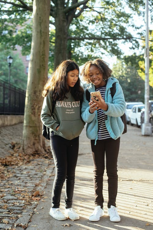 Fröhliche Schulmädchen Mit Smartphone Auf Dem Bürgersteig