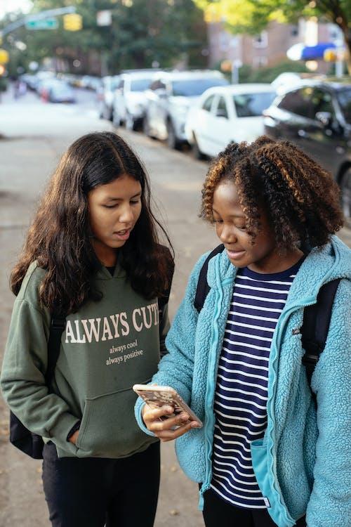 Multiethnische Klassenkameraden, Die Zusammen Auf Dem Smartphone Chatten