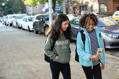 Glückliche Verschiedene Freundinnen, Die Auf Straße Mit Smartphone Gehen