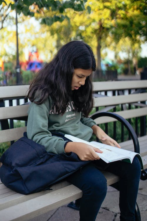 Hispanic child with book on bench