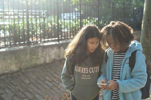 Opgewonden Multi Etnisch Schoolmeisjes Smartphone Browsen Op De Stoep
