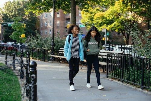 Smiling diverse girlfriends walking in park