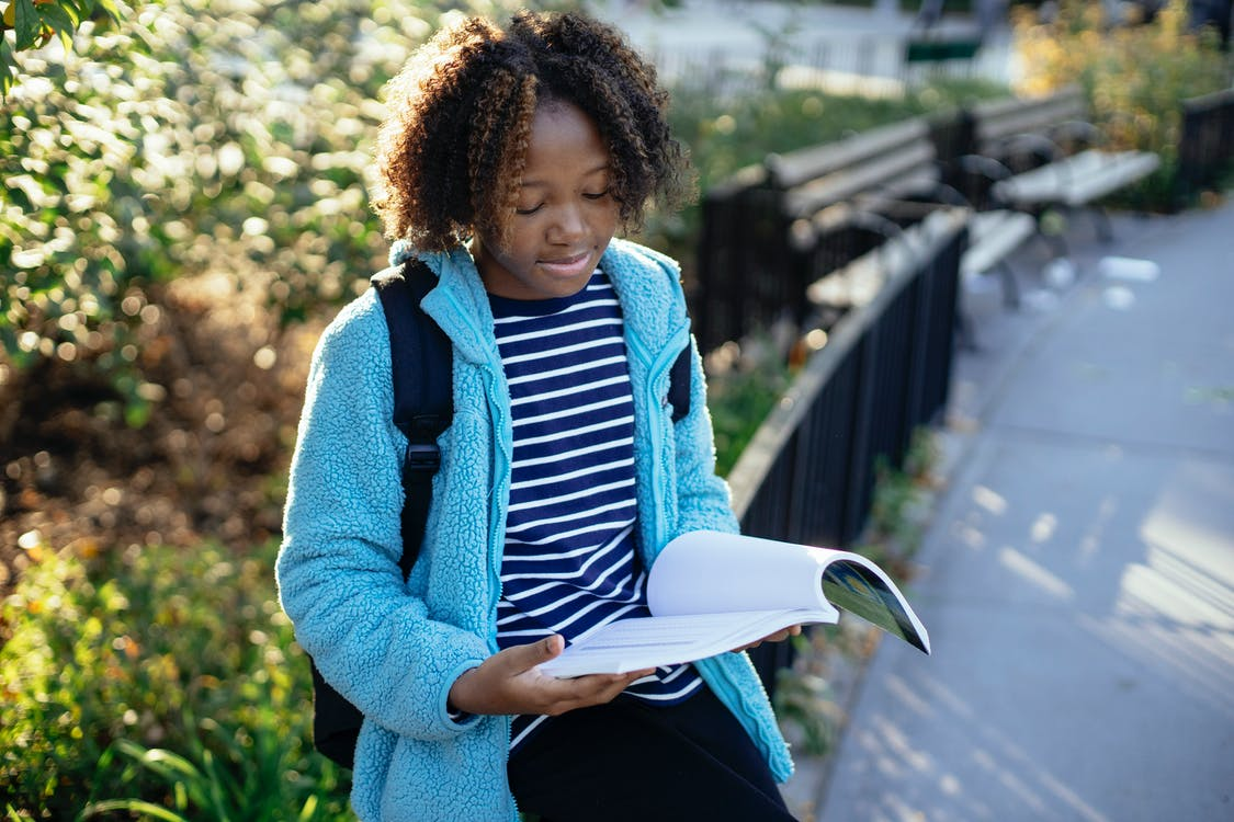African American child in casual clothes with backpack sitting on metal fence and reading book while spending time in park