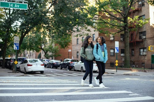 Cheerful schoolgirls crossing road in city