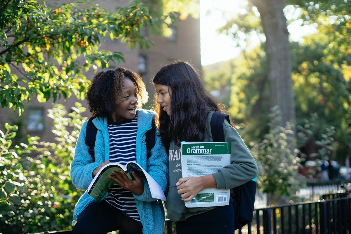 Cheerful multiracial friends in casual clothes with backpacks standing near fence in park while talking about study