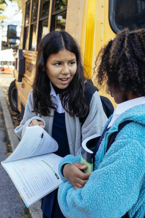 Happy multiethnic children discussing school together