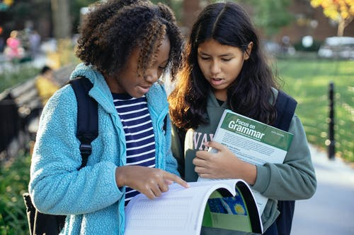 Focused diverse classmates with backpacks holding textbooks and studying while spending time in park